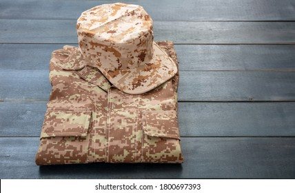 US army cap on a folded uniform, blue color wooden background. Military camouflage digital desert pattern shirt and head gear