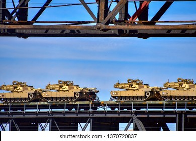 US Army M1 Abrams tanks being transported by railroad over an old trestle bridge.