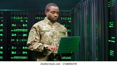 US army male African American officer in uniform stading at server wih secret data and using laptop computer to check the information. Military monitoring service room. Army networking concept.
