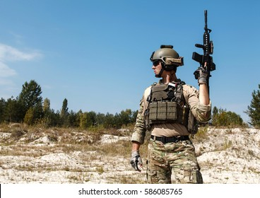 US Army Ranger with weapons in the desert. Plate carrier, eyewear goggles and combat helmet are protecting him