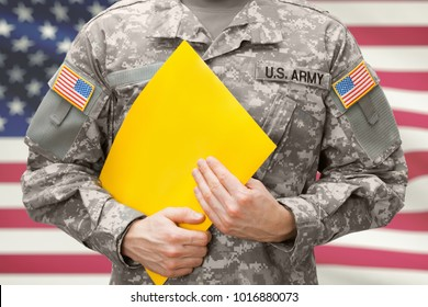 U.S. army soldier holding yellow folder in hands