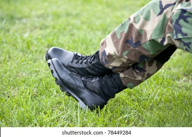 A US Army soldier wearing camouflage resting with just a closeup of his legs and boots, selective focus on boots