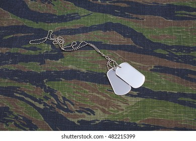 us army tiger stripe camouflaged uniform with blank dog tags background