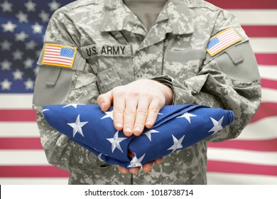 U.S. Army young soldier holding carefully folded USA flag before his chest