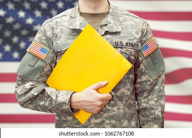 U.S. army young soldier holding yellow folder in left hand