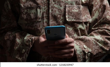 US Army. Young soldier holding a mobile phone standing on dark background