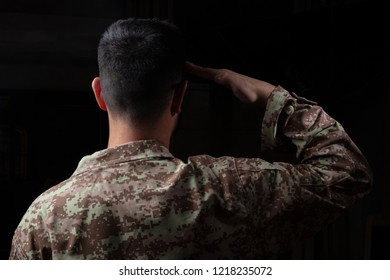 US Army. Young soldier saluting standing on black background