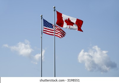 us and canadian flag blowing in the wind on blue sky