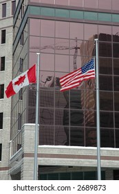 US and Canadian flag in front of building, reflection of construction crane in glass