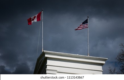 The US and Canadian flags flutter together on top of the Peace Arch border crossing between British Columbia and Washington State. A gloomy, brooding sky is visible in the background.