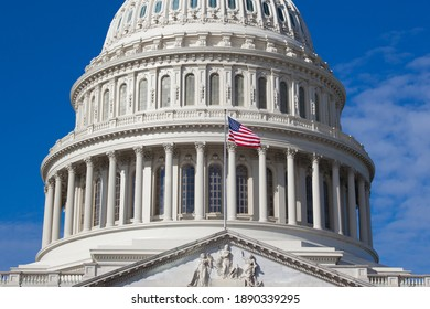 US Capitol is close up. American flag is on the background of the dome of the building of the US Congress