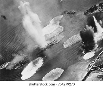 U.S. carrier planes bomb Japanese cruisers anchored in the Kure Harbor Naval Base at Honshu. The warship under attack is almost completely hidden by water geysers from near misses. July 1945. World Wa