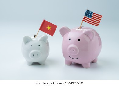 US and China finance, economics or trade war concept, pink piggy bank with USA national flag standing with small white one with China flag on white background.