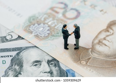 US and China financial tariff trade war negotiation talk, collaboration or discuss concept, miniature people businessman leader handshaking on Chinese yuan banknotes and US dollar.