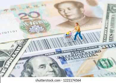 US and China trade, import or export retail ecommerce shopping concept, miniature people figurine with grocery in the shopping cart rally on the bar code with USA Dollar and Chinese Yuan banknotes.