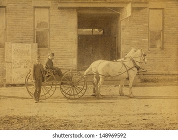 US - Circa 1880 - A vintage photo of three men with a horse drawn wooden wheeled wagon. The wagon is drawn by two white horses and is sitting in front of a building. The street is made of dirt.