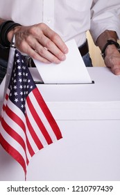 A U.S citizen casting a vote. USA flag in front of the ballot box