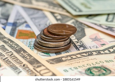 Us coins- five cents, ten cents, quarter, half and one dollar on the background of paper dollar bills