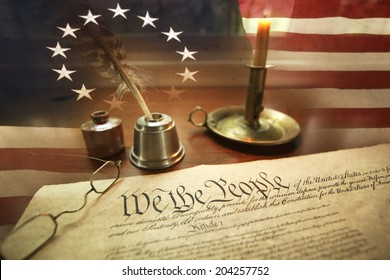 US Constitution with quill pen, ink, glasses, candle and flag with thirteen stars