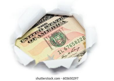 US currency macro peeking through torn white paper.