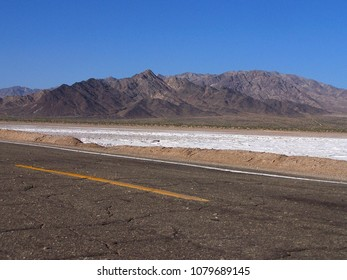 U.S. Desert Road with a Salt Lake and Mountains in Background