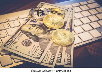 US dollar 100 banknotes and Cryptocurrency, lighting and focusing on gold Bitcoin on white modern keybord and wooden table, dark tone. Concept of transfer or exchange digital money through blockchain.