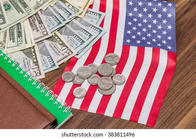 us dollar banknote with coins and flag, notepad, pen on table