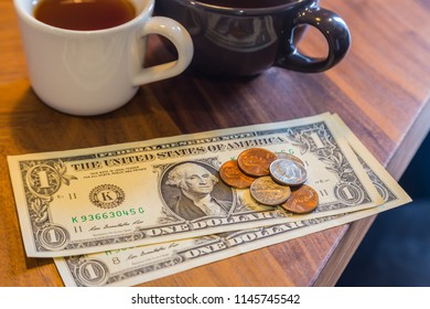 US dollar banknotes and coins on wooden cafe's table, two cups of tea on background, modern and minimal style. Concepts for payment, fee charge, customer service, bill checking, money tips.
