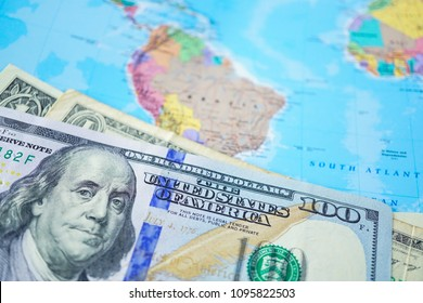 US dollar banknotes on world map background.