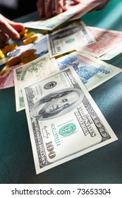 Us dollar bill with several foreign money on the table with people hand doing accounting on background