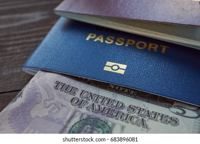 us dollar currency and ID foreign passport for travel on a wooden table. closeup shot