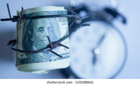 US Dollar money wrapped in barbed wire against clock background as a symbol of economic warfare, sanctions and embargo busting
