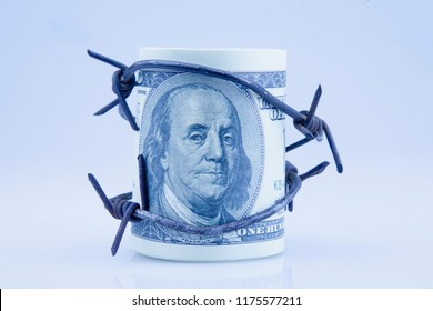 US Dollar money wrapped in barbed wire as symbol of economic warfare and sanctions