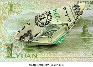 US Dollar paper boat on Chinese banknote