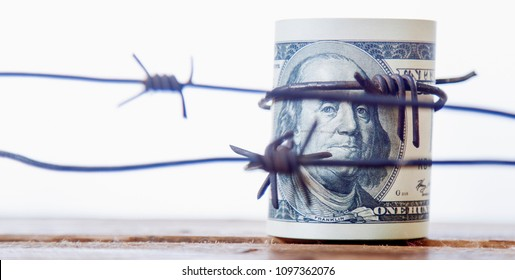 US Dollar wrapped in barbed wire as symbol of economic warfare, sanctions and embargo busting