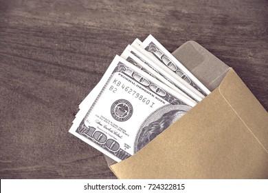 US dollars banknote in envelope on wood table