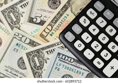 US Dollars banknotes under a black calculator.