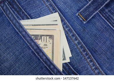 US dollars in blue jeans back pocket
