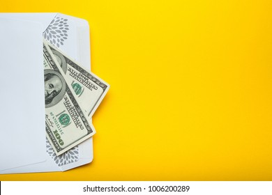 US dollars in an envelope isolated on a yellow background. Empty space for text.