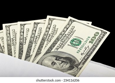 US dollars in an envelope on a black background