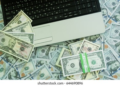 U.S. dollars. Lots of banknotes with laptop. One hundred, fifteen, ten, five and one dollar denominations