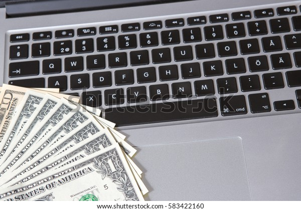 US dollars and a modern laptop. Business and online shopping concept image.