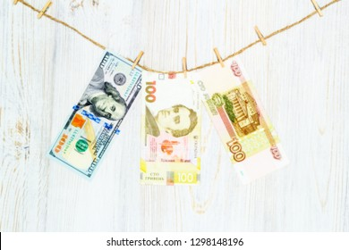 US dollars, Ukrainian hryvnia and Russian rubles suspended on clothespins to the rope. Money laundering, currency fraud and corruption concept