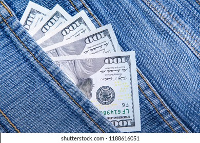 US dollars are visible in the pocket. 100 dollar bills sticking out of a jeans denim pocket. One hundred dollar bills. Money in your pocket. Business concept exchange. Wealth in pants.Good luck smile.