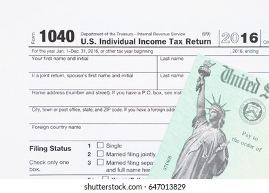 A US Federal tax 1040  income tax form with money and refund check