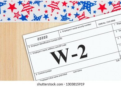 A US Federal tax W2 income tax form on a desk with USA banner