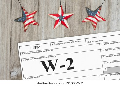 A US Federal tax W2 income tax form on weathered wood with USA stars