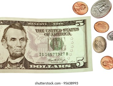 A US five- dollar bill and falling coins on a white background.
