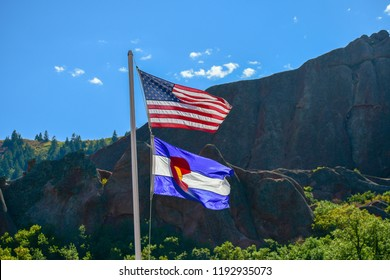 The US Flag and Colorado State Flag proudly wave in the breeze in the mountains of Colorado USA
