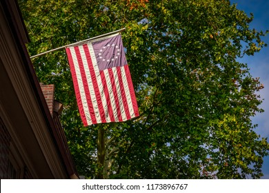 The US flag commonly referred to as the Betsy Ross Flag as seen from the street as it hangs from a building in Philadelphia, PA.